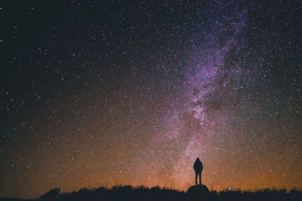 header image - person standing on top of a mountain on dark, starry night