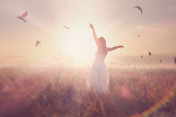 header image - woman standing in field at sunrise
