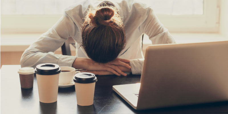 header image - woman with head down on desk and coffee cups around her