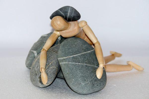 wooden mannequine stuck under some grey rocks.