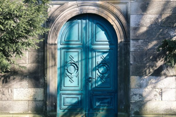 A pretty turquoise door that is closed.