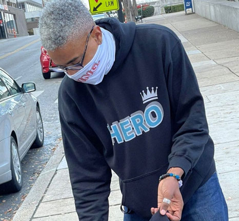 Sekou Writes, creator of Hero Hoodies wearing a black Hero Hoodie. Sekou Writes gives one new Hero Hoodie to the Unhoused with every purchase of a Hero Hoodie.